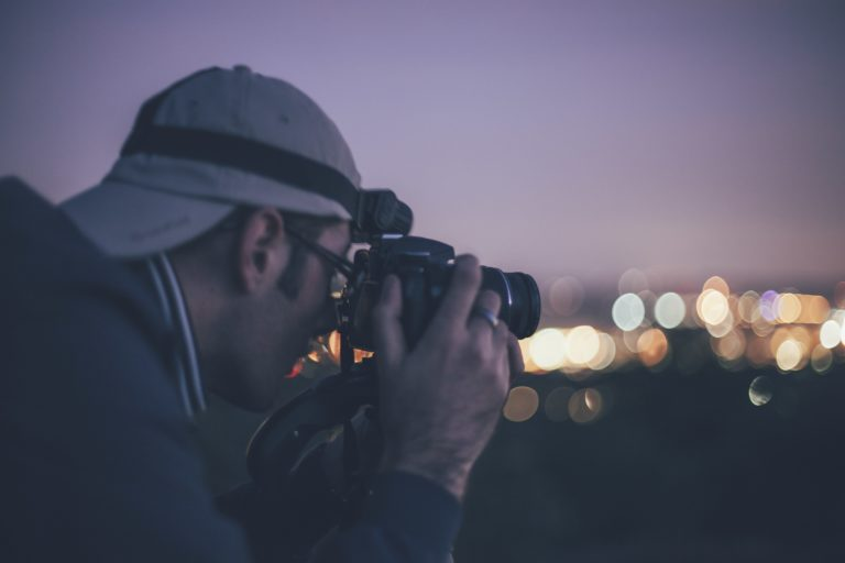 man taking photograph at night