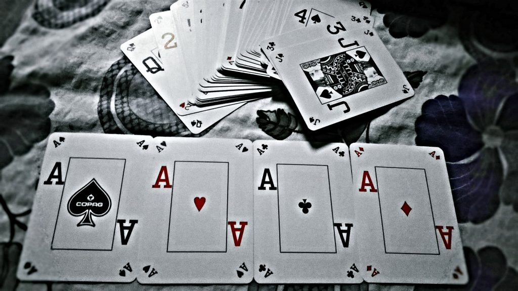 4 aces played on table, deck of cards
