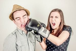 playful fighting, woman hitting man with boxing glove